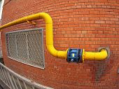 stock photo of gas-pipes  - Wall of a building with a yellow gas pipe and a large valve with wide angle fisheye view - JPG
