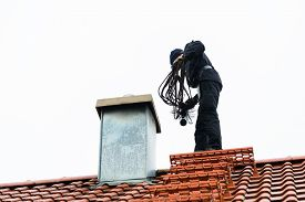 pic of sweeper  - Chimney sweep standing on roof of home working - JPG