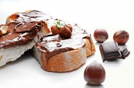 stock photo of hazelnut  - Two slices of bread with chocolate cream and hazelnuts white isolated front view - JPG