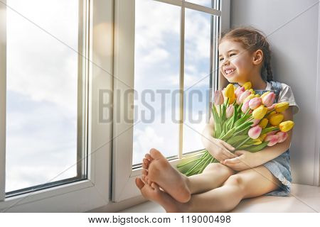 Adorable little child girl sitting on the window and holding tulips. Girl looks at the blue, pure sky and rejoices to spring and sun.