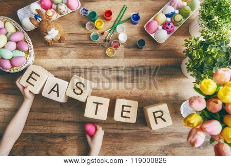 Happy easter! Child painting Easter eggs. Preparing for Easter. On the table lay the cubes with the words Easter. The view from the top.