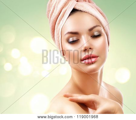 Spa Woman. Beautiful Girl After Bath Touching Her Face. Perfect Skin. Skincare. Young Skin, youth. Beauty female with a towel on her head pampering skin