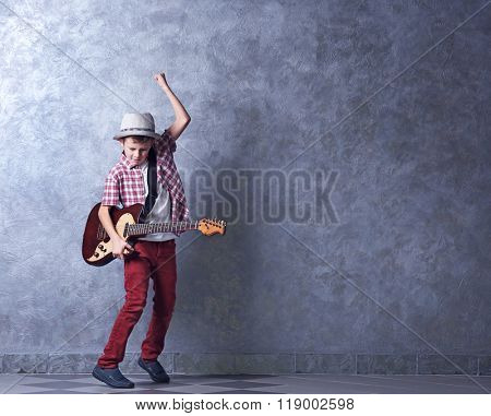 Little boy playing guitar on a grey wall background