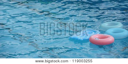 Float Rings Are In Bright Blue Water Of Swimming Pool.