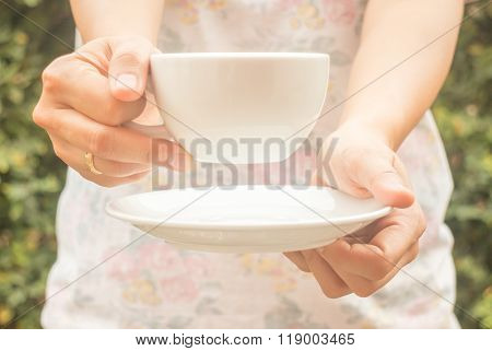 Hand On Cup Of Coffee With Vintage Filter