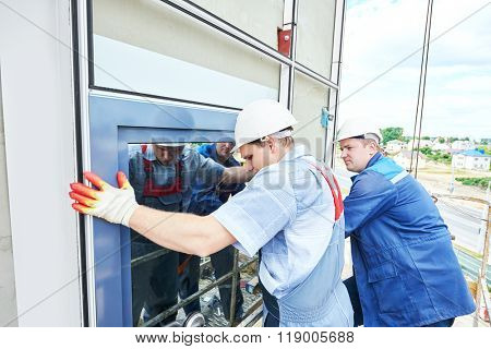 builders worker installing glass windows on facade