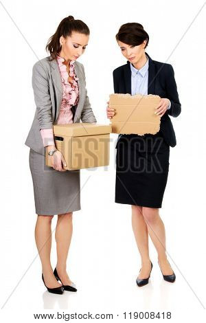 Two sad businesswoman carrying box.