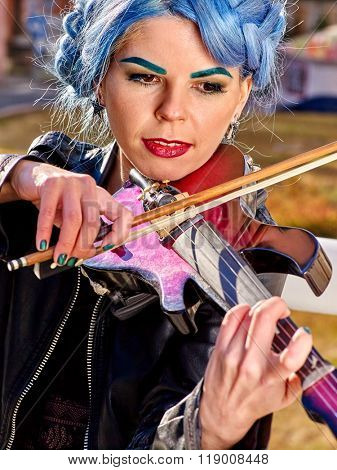 Portrait of music street performers girl violinist with blue hair playing  outdoor.