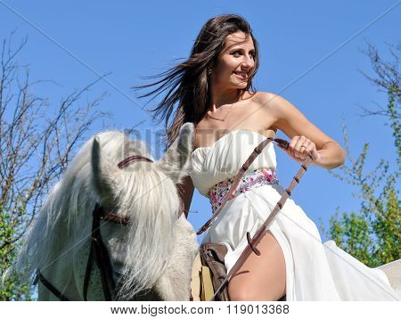 Young Attractive Woman In White Dress With White Horse