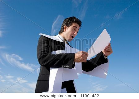 Businessman looking over paperwork with a surprised expression
