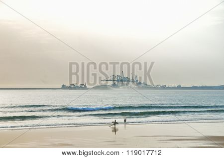 Surfer and peoples on the beach with industrial harbor on background