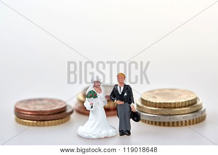 Figurine Wedding Couple In Front Of Money Stack