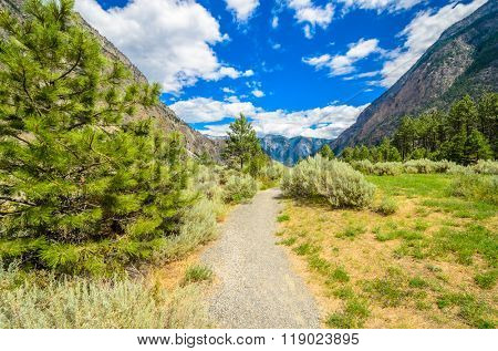 Beautiful landscape of valley in Alpine mountains, small trail, hike root, majestic picturesque view in sunny day. Lillooet Seton Lake. Vancouver. British Columbia. Canada.