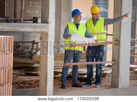 Two male architects show building place and discus with colleague architect, male