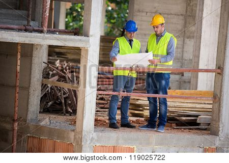 Two male architects look at blue print on open air building construction architect, male, look,