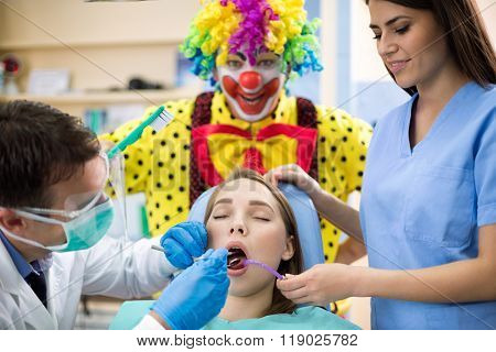 Female patient repair tooth in dental clinic with silly clown in background holding toothbrush