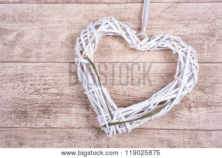 White Heart From Wickerwork With Grass On Wooden Background