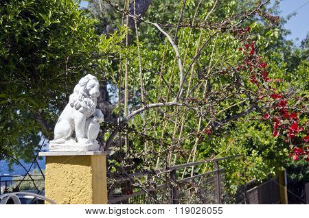 Sculpture Of Lion By The Bougainvillea