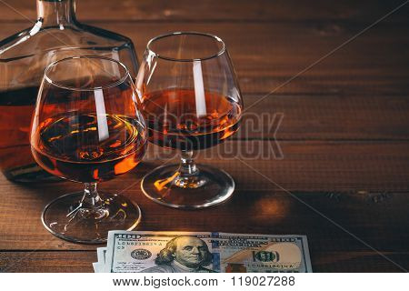 Two Glasses Of Cognac And Bottle, With Wad Of Money On The Wooden Table.