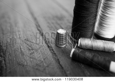 Sewing accessories: bobbins of thread, needle, thimble on wooden table. Black and white photo. Tailo