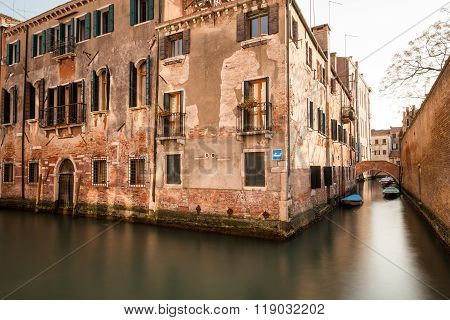 A side view of old buildings along the Venice Canals during the day. Boats can be seen.