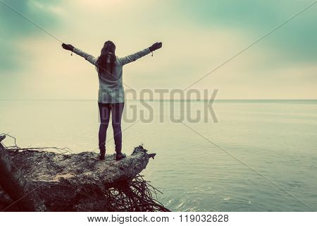 Woman standing on broken tree on wild beach with arms raised looking at sea. Vintage, conceptual.