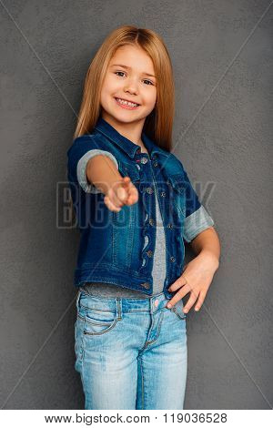 I choose you! Cheerful littlegirl pointing you and looking at camera with smile while standing against grey background
