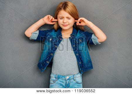 I am not listening! Beautiful littlegirl covering ears with hands and keeping eyes closedwhile standing against grey background