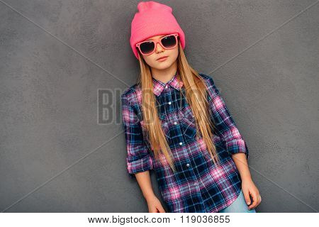 Confident little miss. Beautiful little girl wearing pink beanie hat looking at camera while standing against grey background