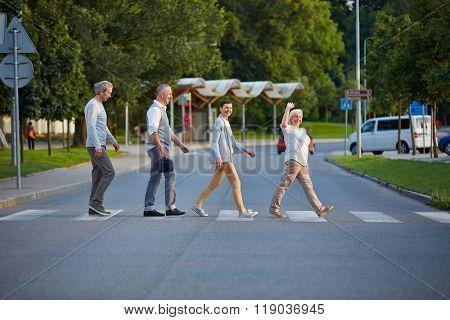 Happy group of seniors walking over crosswalk in a line