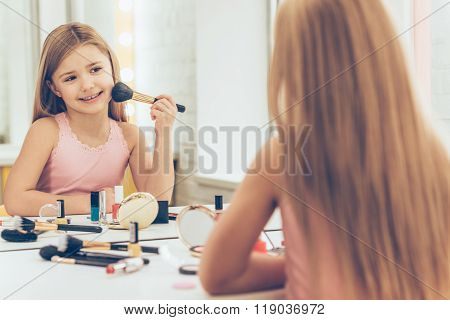 Playing with make-up. Cheerful little girl applying make-up and looking at her reflection in mirror while sitting at the dressing table
