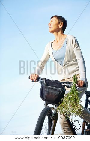 Senior woman on bike tour in summer with her bicycle