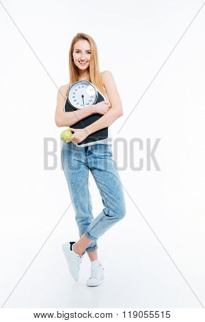 Beautiful joyful young woman posing with scales and green apple over white background