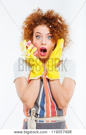 Amazed attractive young woman with foam on her curly red hair in protective gloves holding yellow sponge over white background