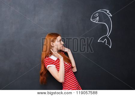 Cute redhead afraid young woman scared of small shark drawn on chalkboard background