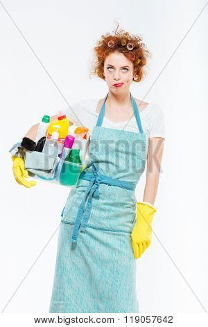 Irritated pretty young woman in yellow gloves holding box with cleansers over white background
