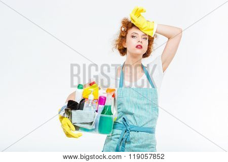 Tired attractive young woman in yellow gloves and blue apron standing and holding box with detergents over white background