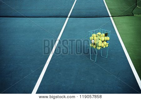 Tennis court with tennis balls in tennis ball basket stand. Intentionally shot in surreal tone.