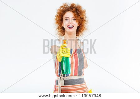 Cheerful pretty redhead young woman in striped apron and yellow gloves holding spray with liquid detergent over white background