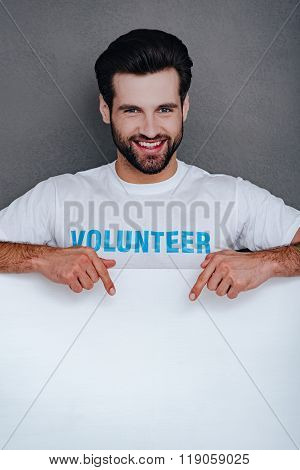 Everything you interested in is here! Confident young man in volunteer t-shirt pointing to white board and looking at camera with smile while standing against grey background