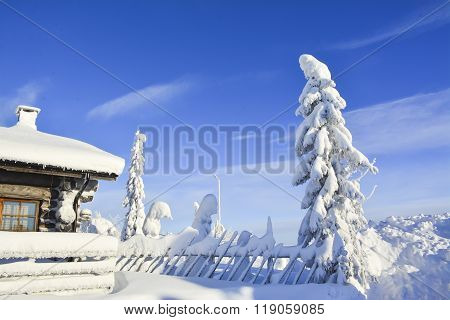 Cottage on snowy mountain on a sunny winter day