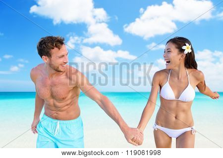 Beach vacation fun sexy couple in bikini swimwear and blue swim shorts on perfect turquoise ocean background. Happy people holding hands laughing with slim shape. Weight loss suntan body care concept.