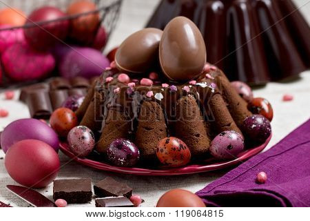 Chocolate Easter Cake And Easter Eggs Colored In Purple And Brown.