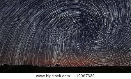 Beautiful Spiral Star Trails over filed with lonely tree. Beautiful night sky