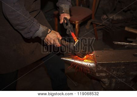 A blacksmith forging hot iron on the anvil