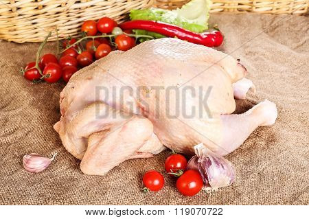 Fresh raw chicken carcass wooden board with tomato