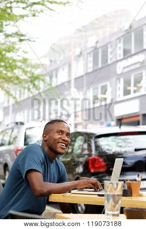 Young African Guy At Cafe With A Laptop