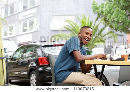 Smiling  African Man Sitting At An Outdoor Coffee Shop
