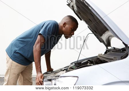 African Guy Looking Under The Hood Of His Broken Down Car