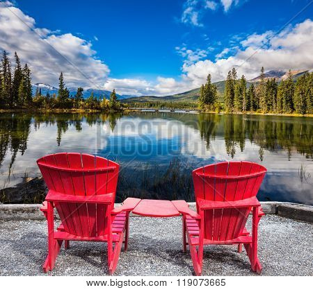 Two red chaise lounges for the tourists connected among themselves by a table. Pyramid Mountain reflected in Pyramid Lake